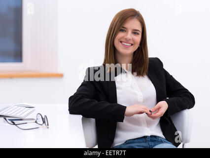Portrait of a beautiful smiling woman sitting in the office - Stock Photo