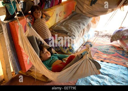 Baby sleeping in hammock, Syrian refugee camp, Lebanon - Stock Photo