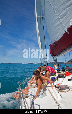 Youngsters sunning on deck of sailing yacht on the Coral Sea near the Whitsunday Islands, Queensland, Australia - Stock Photo