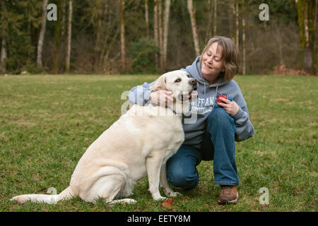 6 year old English Yellow Labrador, Murphy, being affectionate with his sixytish female owner in Issaquah, Washington, - Stock Photo