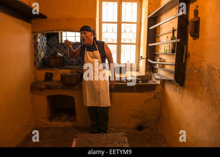Male cook tasting soup in an old-fashioned kitchen - Stock Photo