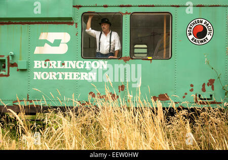 Male in a bowler hat in a railroad car - Stock Photo