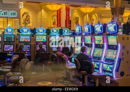 People playing slot machines at the Caesars Palace Hotel and Casino, Las Vegas, Nevada, USA - Stock Photo