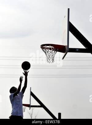 Jayqwan Wilkins of New Haven enjoys the spring-like weather as he played basketball with friends at Criscoulo Park - Stock Photo
