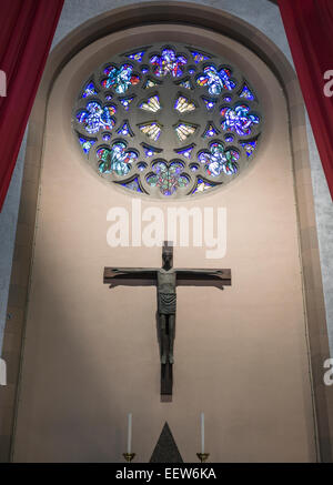 Rose Church Window with Modern Christ on the Cross. The stained glass window of this Roman Catholic Church w modern - Stock Photo