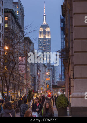 Fifth Avenue with the floodlit Empire State Building in the back. Shoppers crowd the sidewalk while the lights start - Stock Photo