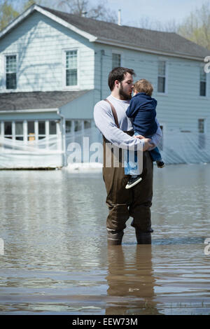 Man with son standing in front of house surrounded by floodwaters - Stock Photo
