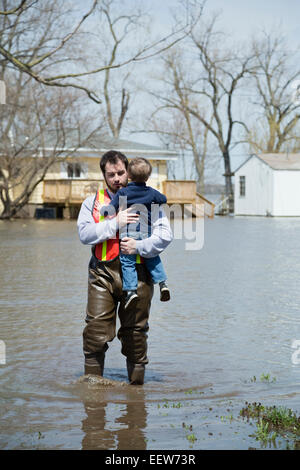 Man with son wading in floodwaters - Stock Photo