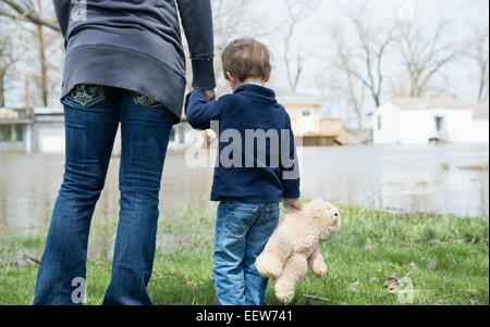 Mother with son standing in flooded town - Stock Photo