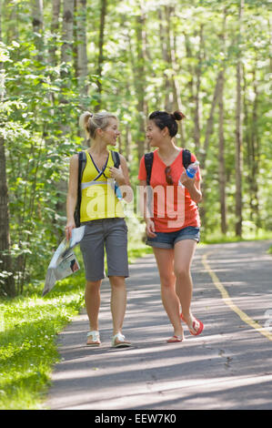 Two girl friends walking on a bike path in the forest - Stock Photo
