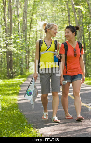 Two girl friends walking on a bike path in the forest with a map - Stock Photo