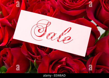 Close-up of red roses with sign 'Sale' - Stock Photo