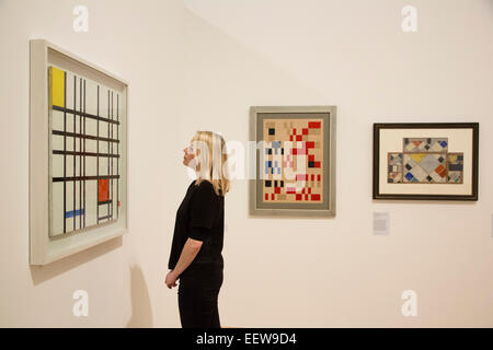 A Whitechapel employee looks at the artworks, from left, 'Composition with Yellow, Blue and Red' by Piet Mondrian, - Stock Photo