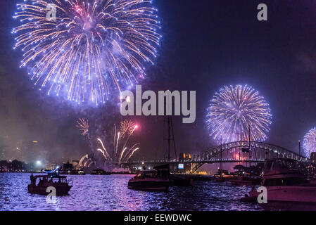 Family Fireworks Display over Sydney Opera House, Harbour Bridge and boats at anchor, New Year's Eve 2014, Sydney - Stock Photo