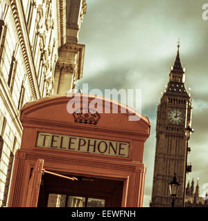 a view of a classic red telephone booth and the Big Ben in the background, in London, United Kingdom, with a filter - Stock Photo