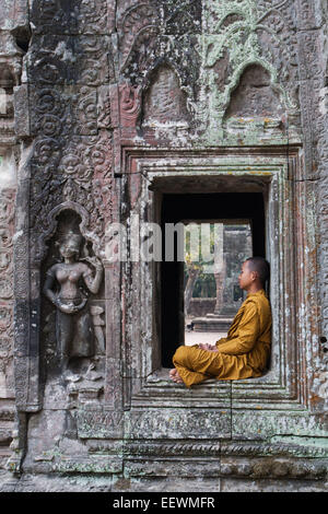 Young  Monk siting in a window at Ta Prohm ruined temple at Angkor Wat ,Cambodia - Stock Photo