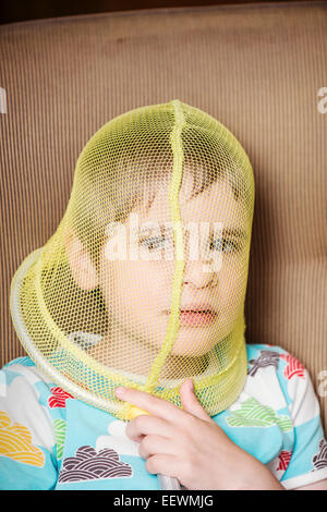 Portrait of girl with net covering her face. She looks troubled and pensive Conceptual image of childhood boredom, - Stock Photo
