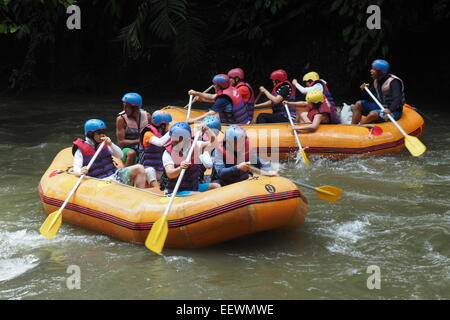 Two groups of people white water rafting on the Ayung River, Ubud, Bali - Stock Photo