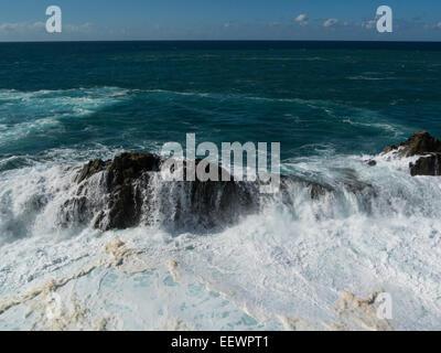 Atlantic rollers crashing over volcanic rocks at Ajuy Fuerteventura Canary Islands on spectacular coastline of Ajuy - Stock Photo