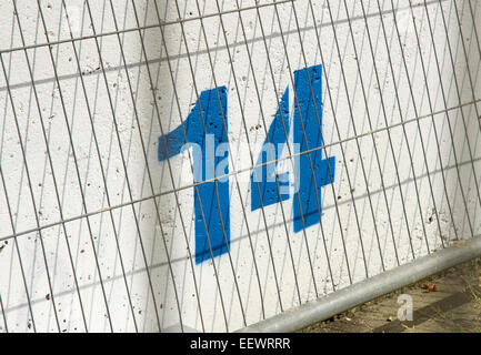 Number 14 fourteen painted in blue on a while concrete wall - Stock Photo