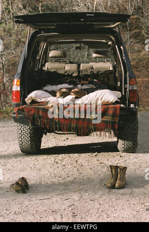 Young couple sleeping in the back of their car, boots standing on the ground in foreground. - Stock Photo