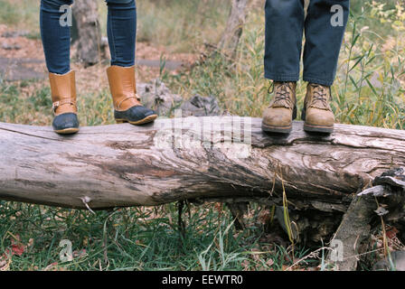 Close up of couple standing side by side on a tree trunk. - Stock Photo