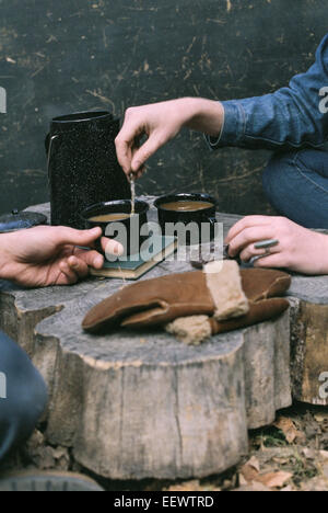 Couple having coffee in a forest, two mugs of coffee, a coffee pot and a pair of gloves on a tree trunk. - Stock Photo