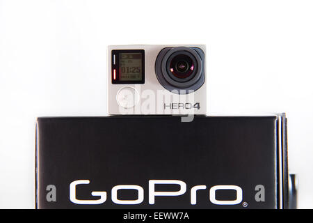 A GoPro Hero 4 Black edition is pictured in a studio on a white background. - Stock Photo