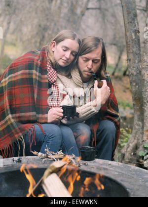 Young couple sitting by a fire pit, wrapped in a blanket. - Stock Photo