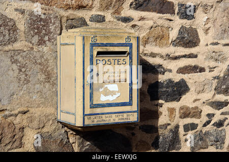 Old yellow French postbox hanging on a wall in Brittany, France - Stock Photo