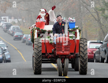 Semour CT USA-- Santa (Jim Chedister of Trumbull) gets a lift from Tom Eighmie of Seymour as Santa visited the party - Stock Photo