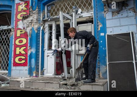 A man cleans broken glass and other debris from a store front damaged after a mortar struck a Donetsk city bus in - Stock Photo