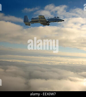 Air Force jet fighter at high altitude above the clouds - Stock Photo