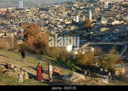 two men on the hill above medina in fez on sunset morocco africa