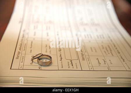 Bride and Groom Silver wedding rings over registry document - Stock Photo