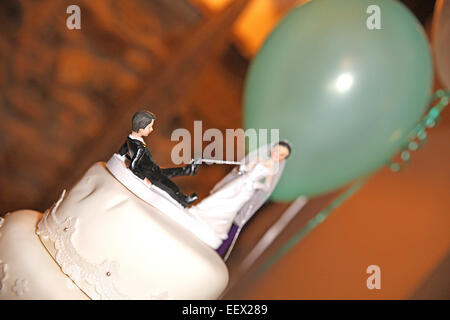 Bride and groom figurines on wedding cake with green balloon in background - Stock Photo