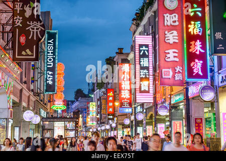 Pedestrians pass through Shangxiajiu Pedestrian Street. The street is the main shopping district of the city. - Stock Photo