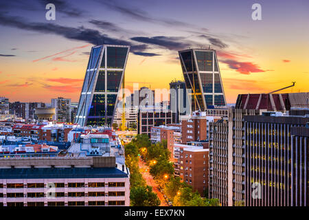 Madrid, Spain financial district skyline at twilight viewed towards the Gate of Europe Plaza. - Stock Photo