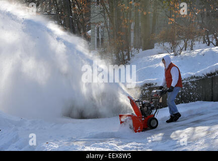 Will Keyes of New Haven helps clear snow off a neighbor's driveway along Hemlock Road in New Haven. - Stock Photo