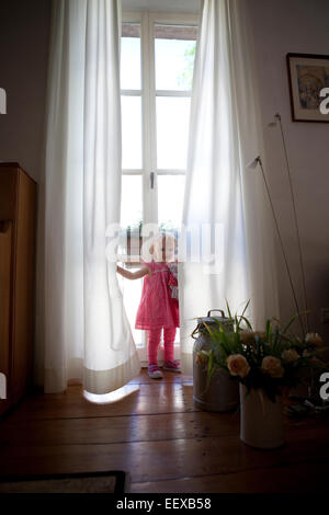 Toddler Playing Peek A Boo Behind Tree Stock Photo