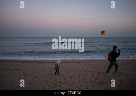 Barcelona, Spain. 22nd Jan, 2015. A man and a child try to fly a kite as the sun sets on the Mediterranean coast - Stock Photo