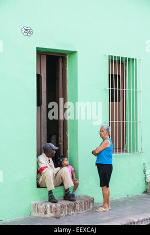 Street life in Camaguey, Cuba's third largest city - two neighbours and a child chat on the doorstep of a green - Stock Photo