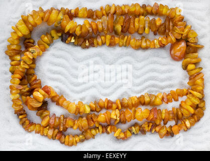 The necklace from the raw amber lies on white pure sea sand. Macro background - Stock Photo