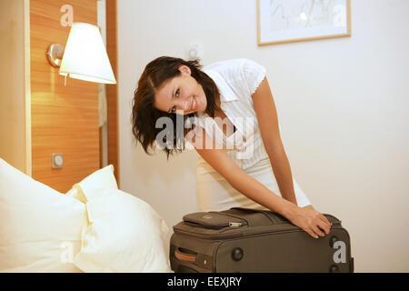 Reisevorbereitung, Frau, Bett, Koffer, packen, Reissverschluss, schliessen, Reisevorbereitungen, Kofferpacken, einpacken, - Stock Photo