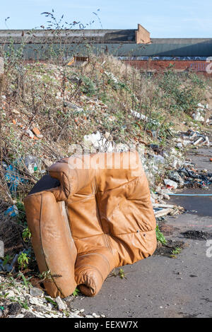 Fly tipping. Illegal dumping of a leather armchair, waste and other rubbish on a pavement on the outskirts of a - Stock Photo