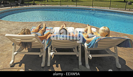 Three girls sunbathing on a poolside in deck chairs - Stock Photo