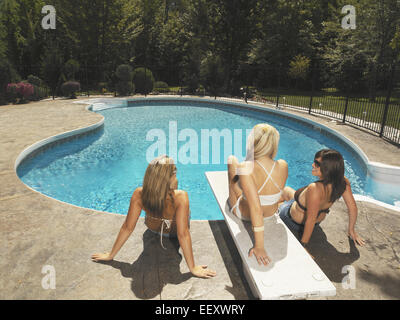 Three girls sitting around a diving board on a pool deck - Stock Photo