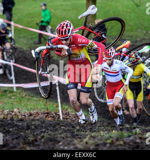 Competitors in a cyclo-cross race carry their bikes up a steep muddy hill section during a race. - Stock Photo