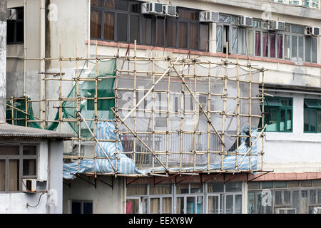 bamboo scaffolding on building height in the streets of Hong Kong - Stock Photo