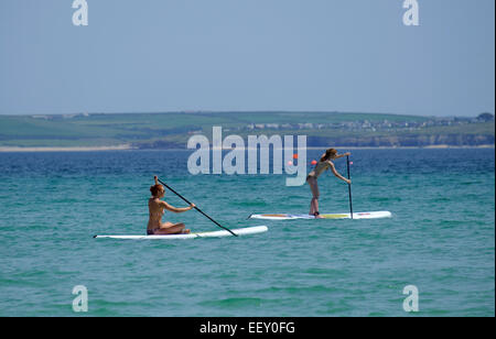 Having fun on Paddle-boards which can be hired on Porthminster beach at St Ives in Cornwall - Stock Photo